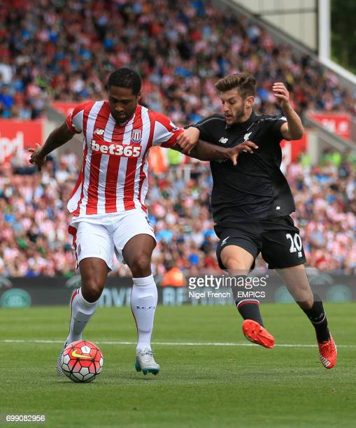 Stoke City's Glen Johnson and Liverpool's Adam Lallana battle for the ball