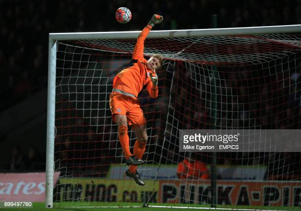 Stoke City's goalkeeper Jakob Haugaard dives in vain as the ball hits the cross bar
