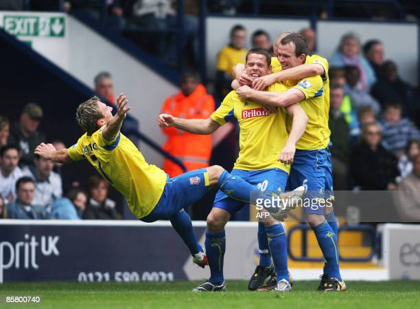Stoke City's James Beattie celebrates scoring the second goal by pushing over teammate Liam Lawrence and Glenn Whelan against West Bromwich Albion...