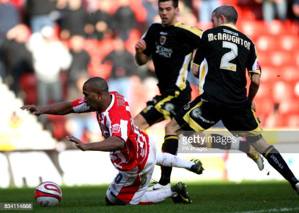 Stoke City's Ricardo Fuller goes down under the challenge of Cardiff City's Kevin McNaughton to win a penalty during the CocaCola Championship match...