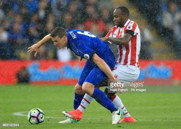 Stoke City's Saido Berahino and Leicester City's Robert Huth battle for the ball during the Premier League match at the King Power Stadium Leicester