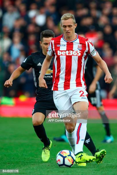 Stoke City's Scottish midfielder Darren Fletcher passes the ball under pressure from Manchester United's Italian defender Matteo Darmian during the...