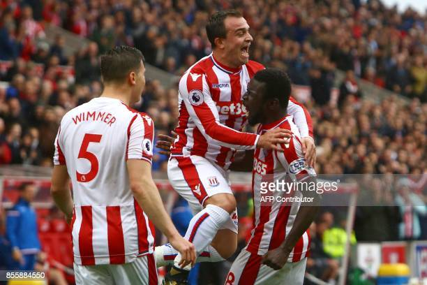 Stoke City's Senegalese striker Mame Biram Diouf celebrates with Stoke City's Swiss forward Xherdan Shaqiri after scoring the opening goal of the...