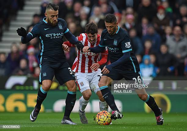 Stoke City's Spanish striker Bojan Krkic is tackled by Manchester City's Argentinian defender Nicolas Otamendi and Manchester City's Argentinian...