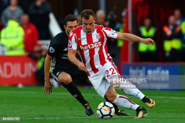 Stoke City's Swiss forward Xherdan Shaqiri controls the ball under pressure from Manchester United's Italian defender Matteo Darmian during the...