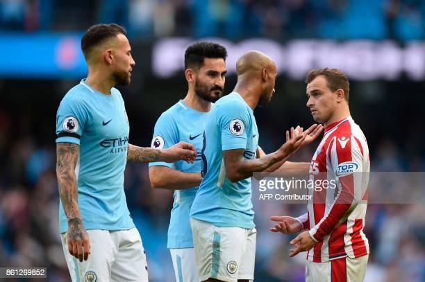 Stoke City's Swiss forward Xherdan Shaqiri talks with Manchester City's English midfielder Fabian Delph at the end of the English Premier League...