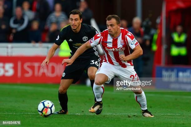Stoke City's Swiss forward Xherdan Shaqiri vies with Manchester United's Italian defender Matteo Darmian during the English Premier League football...