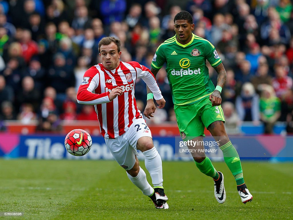 Stoke City's Swiss midfielder Xherdan Shaqiri (L) runs ahead of Sunderland's Dutch defender Patrick van Aanholt (R) during the English Premier League football match between Stoke City and Sunderland at the Britannia Stadium in Stoke-on-Trent, central England on April 30, 2016. / AFP / LINDSEY PARNABY / RESTRICTED TO EDITORIAL USE. No use with unauthorized audio, video, data, fixture lists, club/league logos or 'live' services. Online in-match use limited to 75 images, no video emulation. No use in betting, games or single club/league/player publications. /