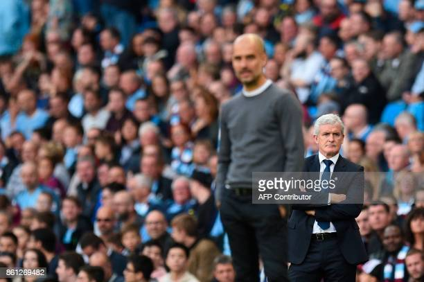 Stoke City's Welsh manager Mark Hughes and Manchester City's Spanish manager Pep Guardiola watch the closing stages of the match from the touchline...