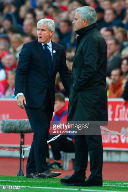 Stoke City's Welsh manager Mark Hughes and Manchester United's Portuguese manager Jose Mourinho look on during the English Premier League football...