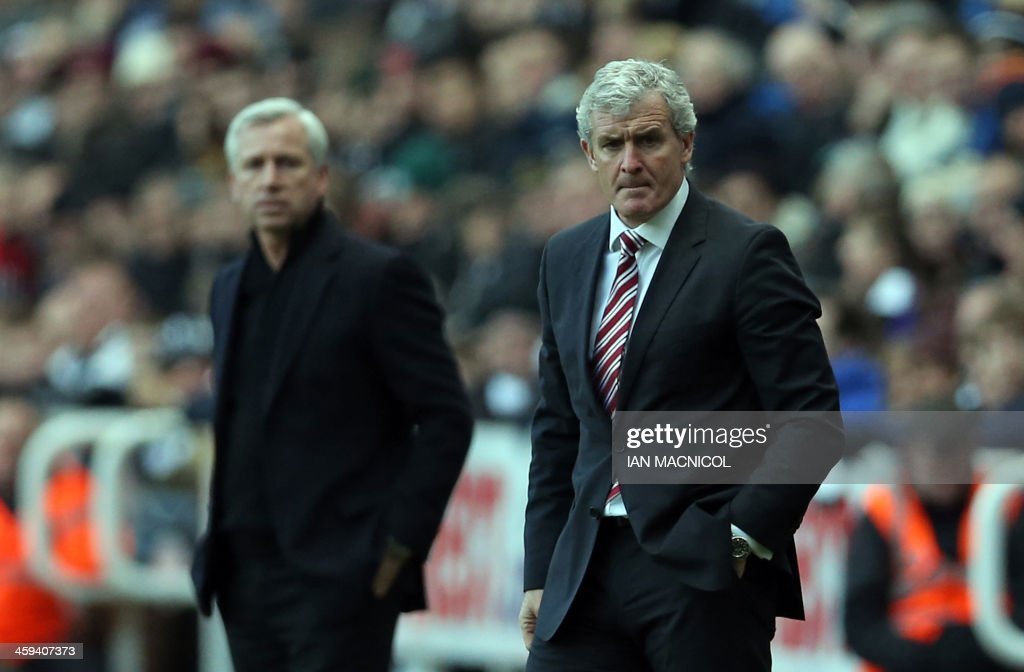 Stoke City's Welsh manager Mark Hughes (R) looks on during the English Premier League football match between Newcastle United and Stoke City at at St James' Park in Newcastle-upon-Tyne, northeast England on December 26, 2013. Newcastle won the game 5-1. AFP PHOTO / IAN MACNICOL USE. No use with unauthorized audio, video, data, fixture lists, club/league logos or live services. Online in-match use limited to 45 images, no video emulation. No use in betting, games or single club/league/player publications.