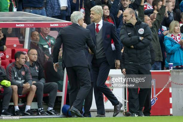Stoke City's Welsh manager Mark Hughes shakes hands with Arsenal's French manager Arsene Wenger after the English Premier League football match...