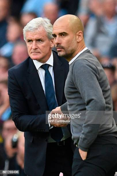 Stoke City's Welsh manager Mark Hughes shakes hands with Manchester City's Spanish manager Pep Guardiola at the final whistle during the English...