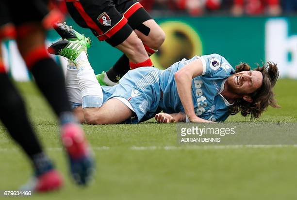 Stoke City's Welsh midfielder Joe Allen reacts after a foul by Bournemouth's Englishborn Irish midfielder Harry Arter during the English Premier...