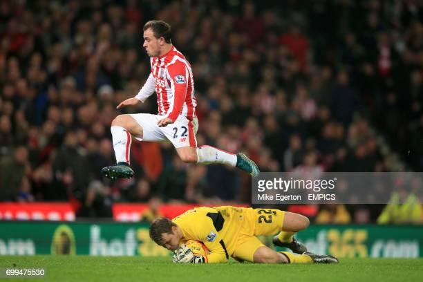 Stoke City's Xherdan Shaqiri hurdles Liverpool goalkeeper Simon Mignolet who claims the ball
