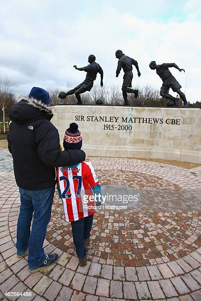 Stoke fans look at The three ages of Sir Stanley Matthews statue is seen prior to the Barclays Premier League match between Stoke City and Queens...