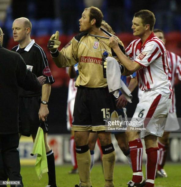 Stoke goalkeeper Steve Simonsen has to be restrained by Clint Hill as he approaches referee Mark Clattenburg at the final whistle to ask about his...