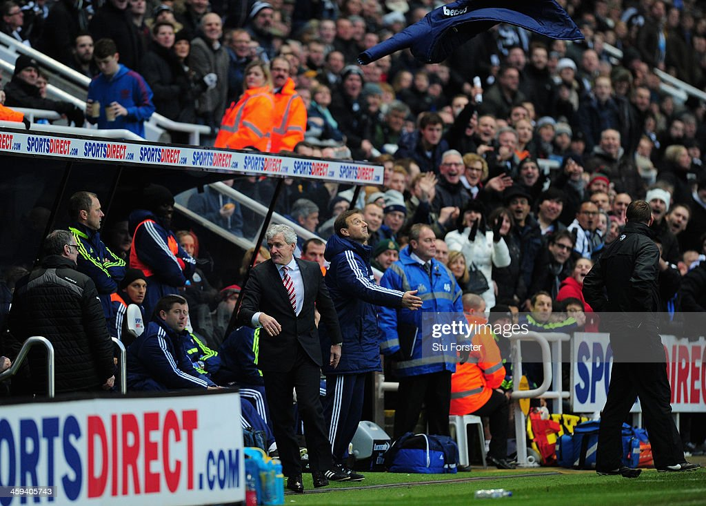 Stoke manager Mark Hughes (l) throws his coat up in the air in disgust after being sent to the stands by referee Martin Atkinson during the Barclays Premier League match between Newcastle United and Stoke City at St James' Park on December 26, 2013 in Newcastle upon Tyne, England.