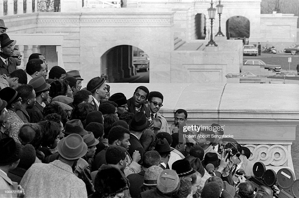Stokely Carmichael (1941 - 1998) and H. Rap Brown speak with supporters who have gathered at the Capitol steps tin support of US Congressman Adam Clayton Powell, Jr., who was stripped of the chairmanship of the Education and Labor Committee, January 1967. News media and reporters are visible among the crowd.