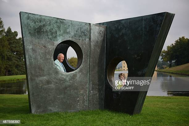 Stoker Cavendish Duke of Devonshire and his wife Amanda Duchess of Devonshire pose by a sculpture by British artist Barbara Hepworth entitled 'Three...