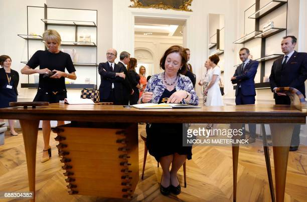 Stoltenberg's wife Ingrid Schulerud signs a guestbook next to Brigitte Macron wife of French President during a visit of the First Ladies to a shop...