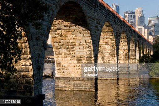 Stone arch bridge over Mississippi river and Minneapolis skyline