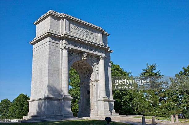 Stone arched monument amid trees under blue skies
