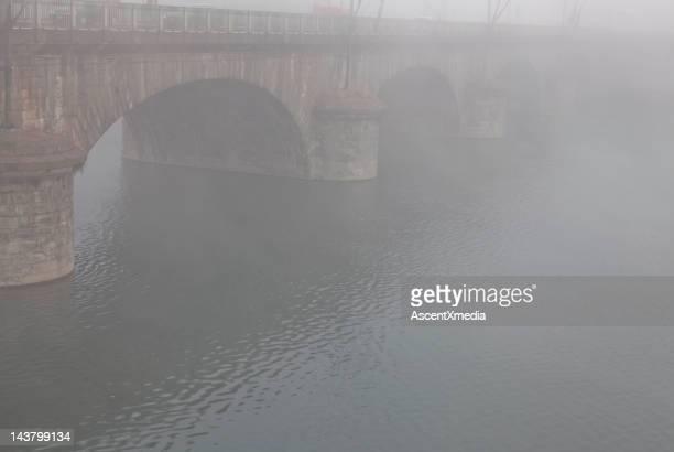 Stone bridge over a river in fog