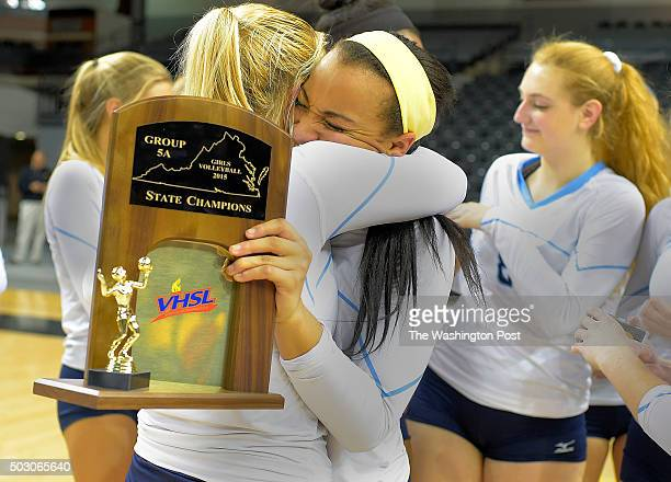 Stone Bridge's Abby DeVido left embraces teammate Ashlyn Dunlop after receiving the Championship trophy after Stone Bridge's defeat of Potomac Falls...