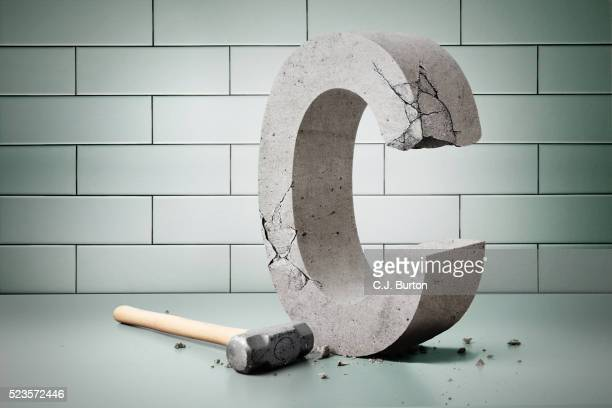 Stone carved letter 'C' and hammer, tiled wall in background