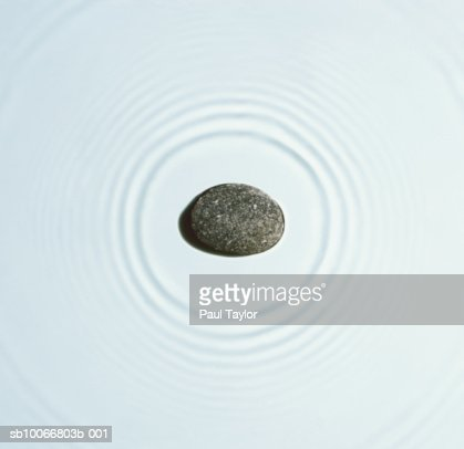 Stone causing ripples on water, close-up