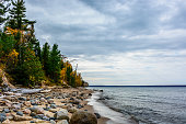 Stone coast in Pictured Rocks National Lakeshore, Munising, MI, USA. Autumn forest on the backghround