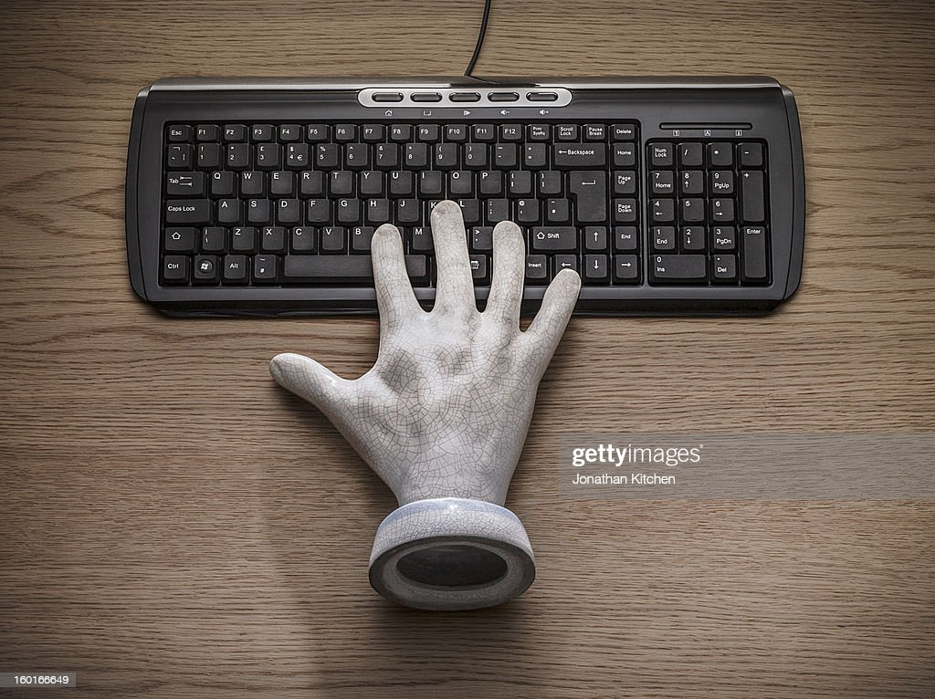 A stone hand on a black keyboard : Stock Photo