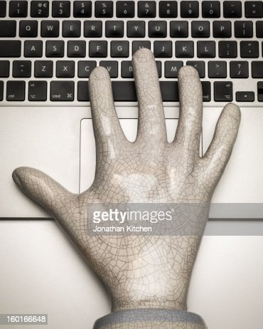 A stone hand rests on a silver computer keyboard : Stock Photo