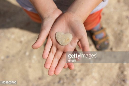 Pedra coração em mãos : Foto de stock
