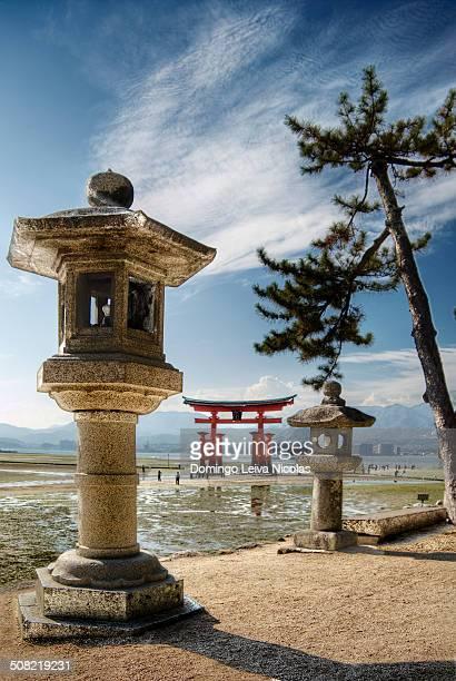 CONTENT] Stone lantern and Torii Gate of Itsukushima Shinto Shrine Miyajima Japan