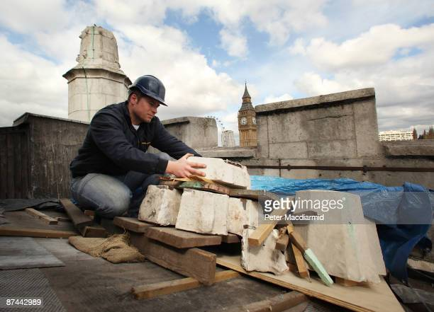 Stone Mason Mark Croll inspects the damaged remains of a stone pinacle on the bell tower roof of St Margaret's Church on May 15 2009 in London St...