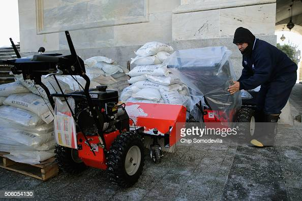 Stone Mason Medaro Romero covers gas powered snow sweepers in plastic bags in preparation for a coming winter storm outside the US Capitol January 21...