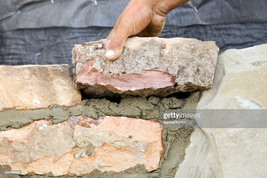 Stone Mason Setting a New Rock on Mortar : Stock Photo
