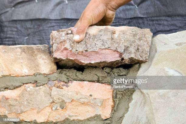 Stone Mason Setting a New Rock on Mortar