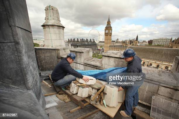 Stone Masons Mark Croll and Joe Goodbody inspect the damaged remains of a stone pinacle on the bell tower roof of St Margaret's Church on May 15 2009...
