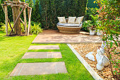 Stone pathway on lawn in the garden with sofa and nature background.