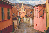 Stone paved old streets with old houses in Sighisoara fortress under the evening sunlight,Transylvania region, Romania