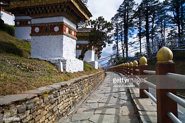 A stone paved walkway encircles a set of chortens on a mountain pass.