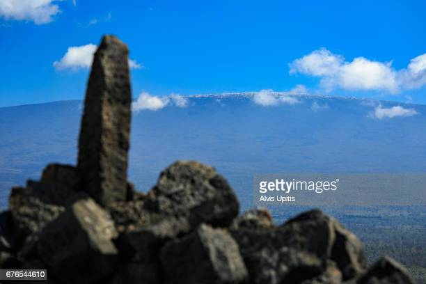 Stone remenants of Umi's Temple against snow dusted Mauna Loa on Hawaii Island.