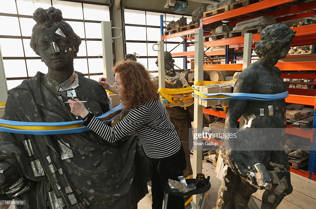 Stone restorer Frauke Herlyn attaches thin sheets of tin to an original sculpture to prepare it for the creation of a casting mould at the Schlossbauhuette studio where a team of sculptors is creating decorative elements for the facade of the Berliner Schloss city palace on February 12, 2013 in Berlin, Germany. The Berliner Schloss was the residence of the Prussian Kaiser and was among the major architectural landmarks of Berlin until it was heavily damaged by Allied bombing in 1945. The communist authorities of East Berlin demolished the building in the 1950s, and today's Berlin government is pursuing an ambitious project to rebuild the palace according to a design by Italian architect Franco Stella, which will recreate the facade of the building but with a modern interior at a cost of approximately EUR 590 million. The Humboldt Forum, the foundation leading the project, has given the Schlossbauhuette sculptors the formidable task of recreating the hundreds of architectural elements that decorated the facade, and though some original pieces were saved, more often the sculptors have only old black and white photos as reference.