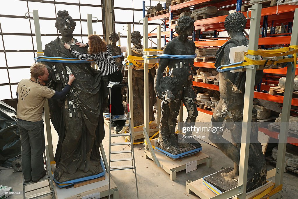 Stone restorers Frauke Herlyn and Anton Gruber attach thin sheets of tin to an original sculpture to prepare it for the creation of a casting mould at the Schlossbauhuette studio where a team of sculptors is creating decorative elements for the facade of the Berliner Schloss city palace on February 12, 2013 in Berlin, Germany. The Berliner Schloss was the residence of the Prussian Kaiser and was among the major architectural landmarks of Berlin until it was heavily damaged by Allied bombing in 1945. The communist authorities of East Berlin demolished the building in the 1950s, and today's Berlin government is pursuing an ambitious project to rebuild the palace according to a design by Italian architect Franco Stella, which will recreate the facade of the building but with a modern interior at a cost of approximately EUR 590 million. The Humboldt Forum, the foundation leading the project, has given the Schlossbauhuette sculptors the formidable task of recreating the hundreds of architectural elements that decorated the facade, and though some original pieces were saved, more often the sculptors have only old black and white photos as reference.
