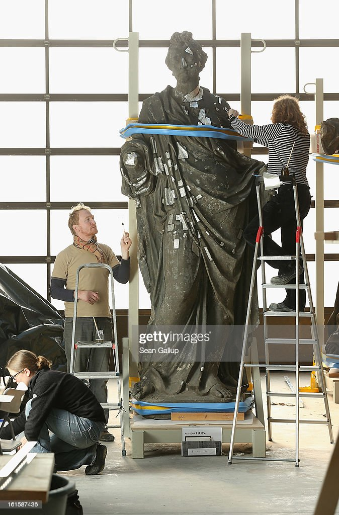 Stone restorers Frauke Herlyn (R) and Anton Gruber attach thin sheets of tin to an original sculpture to prepare it for the creation of a casting mould at the Schlossbauhuette studio where a team of sculptors is creating decorative elements for the facade of the Berliner Schloss city palace on February 12, 2013 in Berlin, Germany. The Berliner Schloss was the residence of the Prussian Kaiser and was among the major architectural landmarks of Berlin until it was heavily damaged by Allied bombing in 1945. The communist authorities of East Berlin demolished the building in the 1950s, and today's Berlin government is pursuing an ambitious project to rebuild the palace according to a design by Italian architect Franco Stella, which will recreate the facade of the building but with a modern interior at a cost of approximately EUR 590 million. The Humboldt Forum, the foundation leading the project, has given the Schlossbauhuette sculptors the formidable task of recreating the hundreds of architectural elements that decorated the facade, and though some original pieces were saved, more often the sculptors have only old black and white photos as reference.