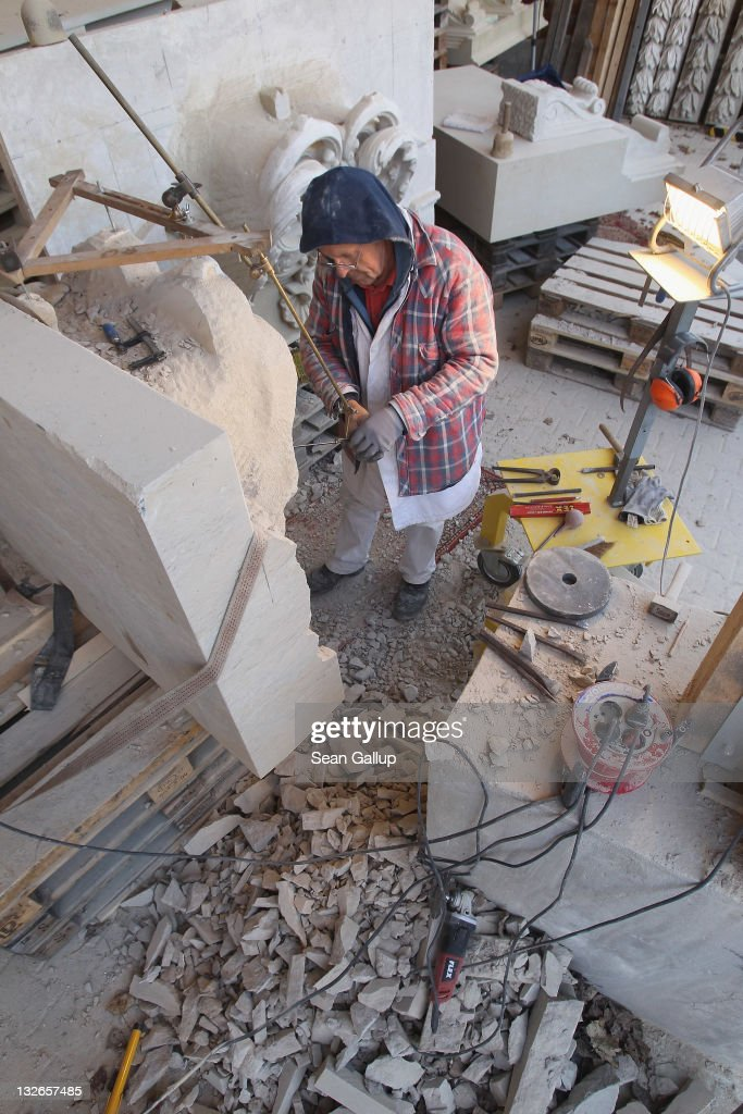 Stone sculptor Carlo Wloch checks proprtions as he copies a gabel decoration in plaster behind him at the Schlossbauhuette studio, where Wloch and a team of sculptors are creating decorative elements for the facade of the Berliner Schloss city palace on November 11, 2011 in Berlin, Germany. The Berliner Schloss was the residence of the Prussian Kaiser and was among the major architectural landmarks of Berlin until it was heavily damaged by Allied bombing in 1945. The communist authorities of East Berlin demolished the building in the 1950s, and today's Berlin government is pursuing an ambitious project to rebuild the palace according to a design by Italian architect Franco Stella, which will recreate the facade of the building but with a modern interior at a cost of approximately EUR 590 million. The Humboldt Forum, the foundation leading the project, has given the Schlossbauhuette sculptors the formidable task of recreating the hundreds of architectural elements that decorated the facade, and though some original pieces were saved, more often the sculptors have only old black and white photos as reference.