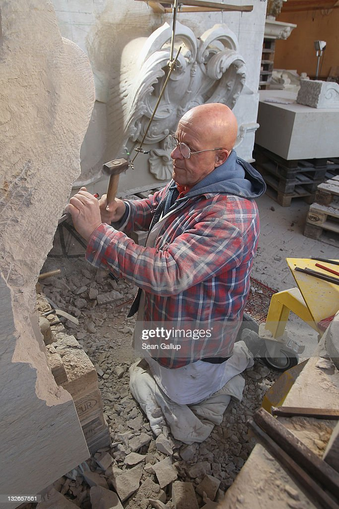 Stone sculptor Carlo Wloch hammers a chisel into sandstone as he copies a gabel decoration in plaster behind him at the Schlossbauhuette studio, where Wloch and a team of sculptors are creating decorative elements for the facade of the Berliner Schloss city palace on November 11, 2011 in Berlin, Germany. The Berliner Schloss was the residence of the Prussian Kaiser and was among the major architectural landmarks of Berlin until it was heavily damaged by Allied bombing in 1945. The communist authorities of East Berlin demolished the building in the 1950s, and today's Berlin government is pursuing an ambitious project to rebuild the palace according to a design by Italian architect Franco Stella, which will recreate the facade of the building but with a modern interior at a cost of approximately EUR 590 million. The Humboldt Forum, the foundation leading the project, has given the Schlossbauhuette sculptors the formidable task of recreating the hundreds of architectural elements that decorated the facade, and though some original pieces were saved, more often the sculptors have only old black and white photos as reference.